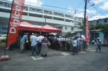 People gather in lines in front of Digicel boothes in Roseau Dominica.jpg